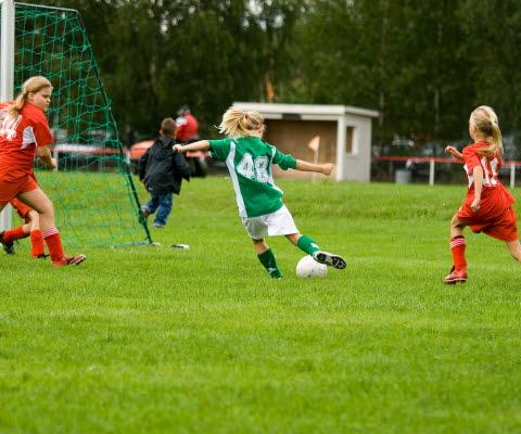 Barn som spelar fotboll.