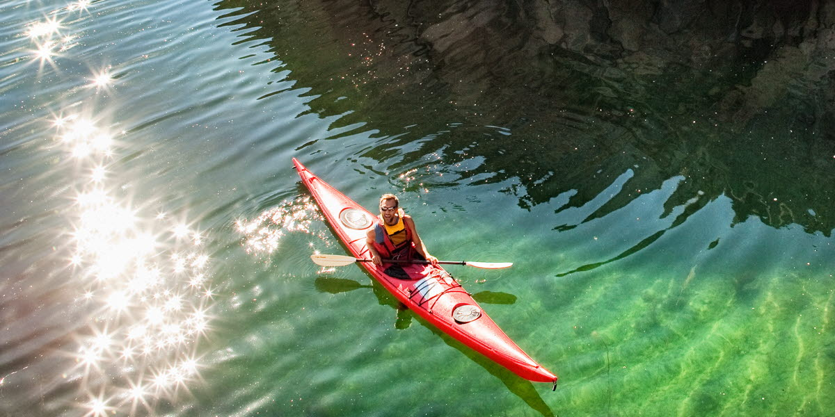A red kayak is paddeling past a cliff. It's a sunny day and the water is clear.