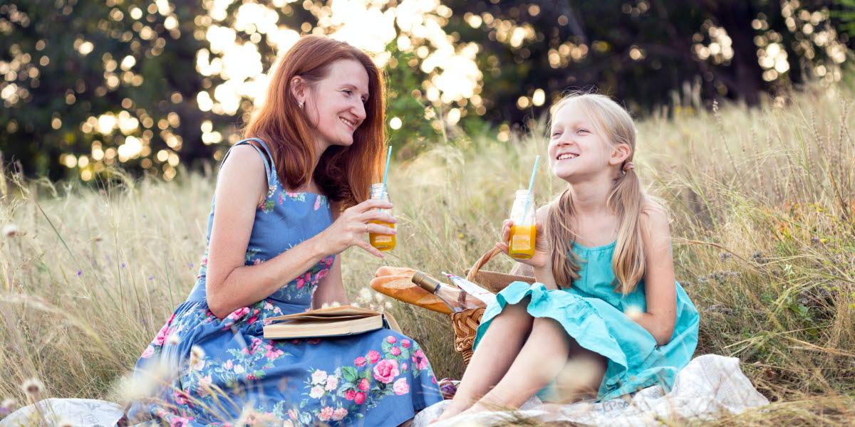 Mamma och dotter har picknick i en skogsdunge.