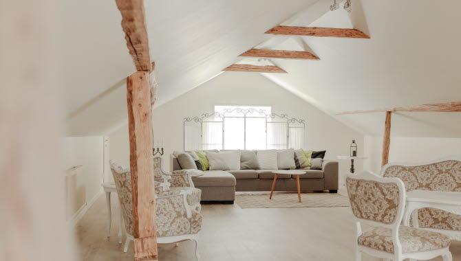 Rum med vitt snedtak och en soffa i grått tyg.
