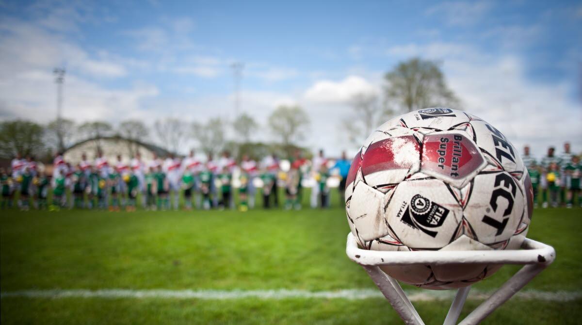 Fotboll på piedestal. Fotbollsspelare i bakgrunden.