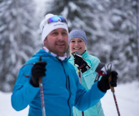 En tjej och kille som är klädda i skidutrustning för längdskidor kollar in i kameran.