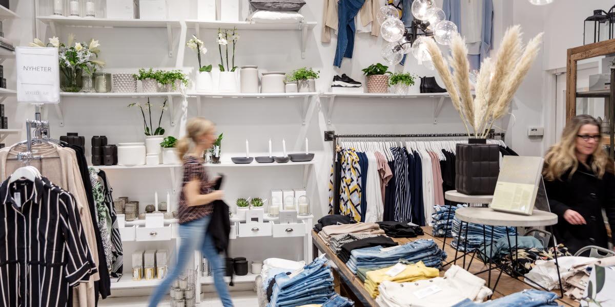 En ljus och fräsch butik med jeans uppradade på ett bord. I butiken finns hyllor med vita inredningsdetaljer. Två kvinnor kikar runt i butiken.