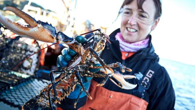Women holding a lobster.