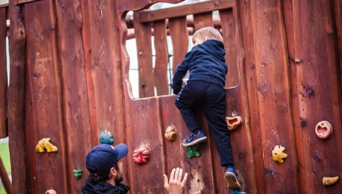 Ett barn som klättrar på en klättervägg på aktivitetsplats äventyret med sin pappa,