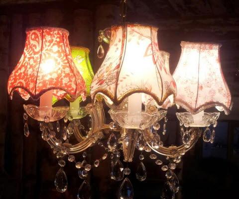 Taklampa med hängande kristaller och skärmar i olika färger och mönster.