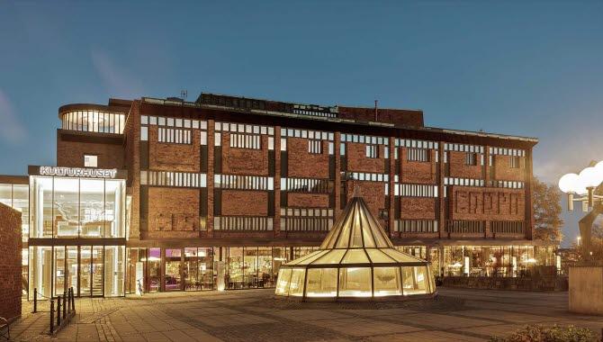 Skövde Kulturhus i kvällsskrud. Från alla fönster i tegelhuset lyser ett varmt gult ljus.