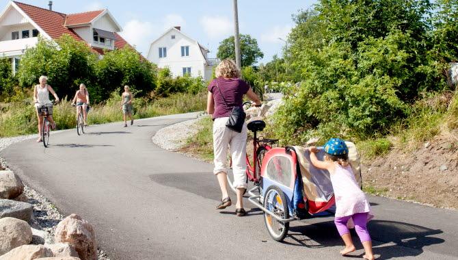 En mamma och ett barn kämpar sig upp för en backe vid Ekenäs med en cykel och en cykelkärra. Mamman leder cykeln och barnet puttar på kärran.