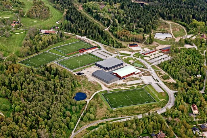 Vy från höjden över grönområde med flera sporthallar och planer