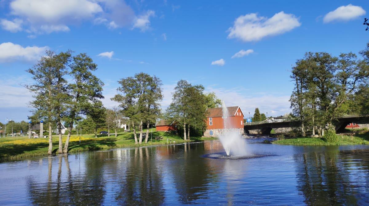 En fontän som sprutar vatten i en å. Ett rött hus i bakgrunden med flera gröna träd runtomkring. Blå himmel.