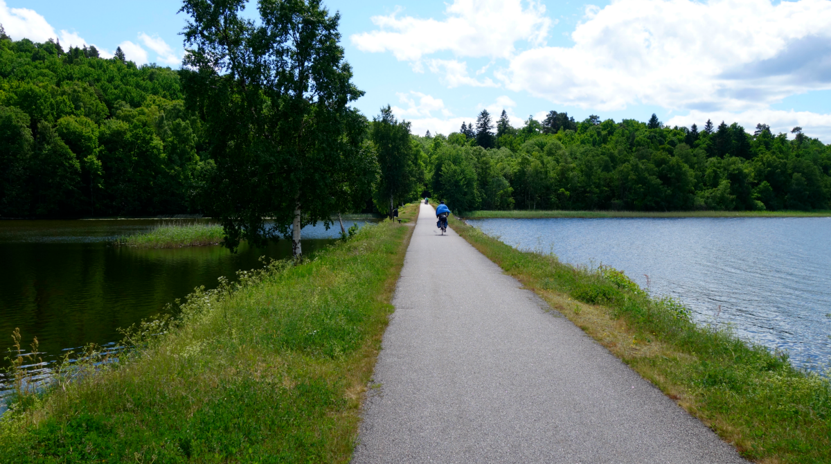 A paved cycle path with water on both sides