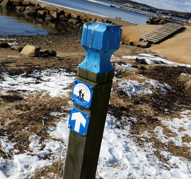Vid Seläter står en träpåle med blåa detaljer som visar vägen för vandringsleden Kuststigen. På marken ligger det det ett tunt lager snö.