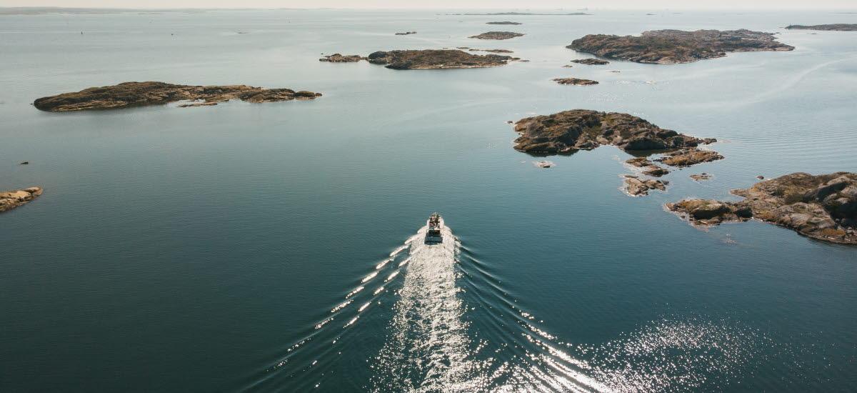 Båt stävar ut mellan öarna ut mot havet