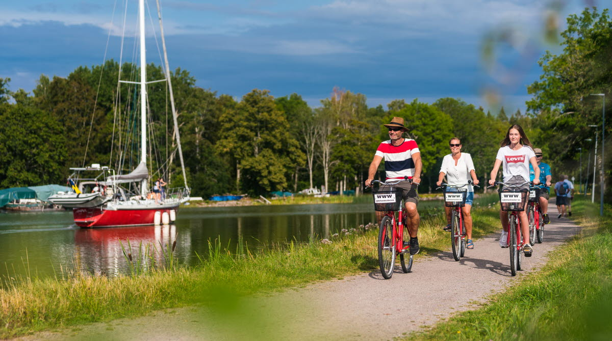 Summer dressed persons cycling along the Göta Canal passing a red sailboat in the canal.