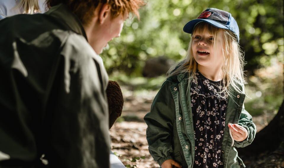 Liten blond flicka i keps tittar och lyssnar fascinerat på Skogsmulle