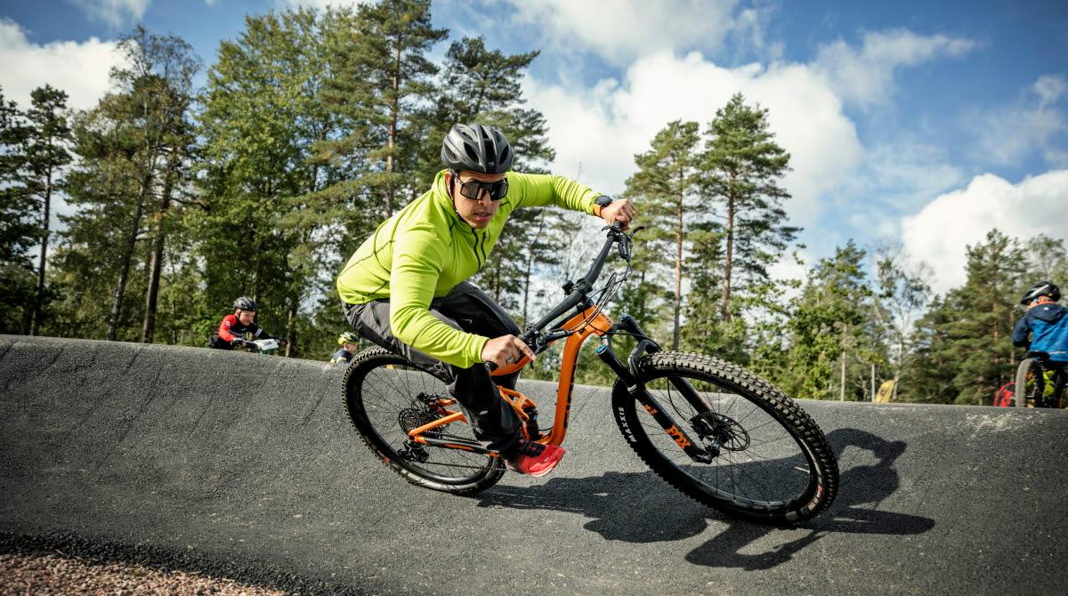En kille i neongul jacka, solglasögon och svart cykelhjälm cyklar på sin orangea cykel på en asfaltsbana, en pumptrackbana. I bakgrunden ser man Billingens skogar.
