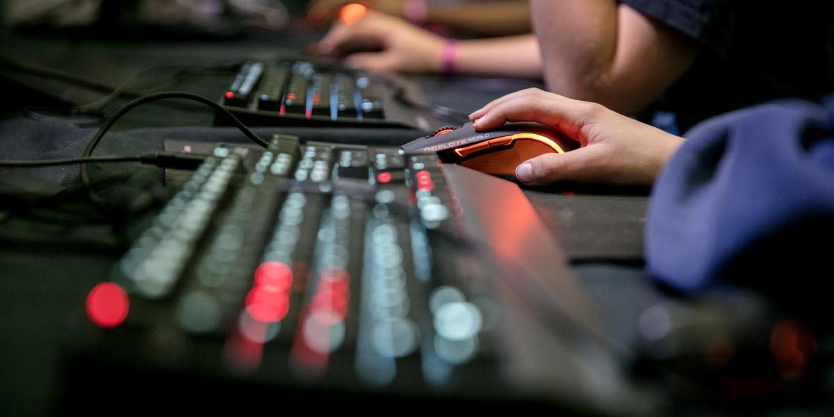 Närbild på ett tangentbord och en hand som håller i en datormus