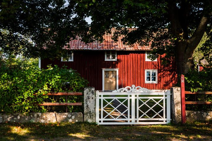 Ett rött hus med vita knutar och gul vacker dörr står omgivet av en lummig trädgård som väntar innanför en vit grind med snickarglädje på toppen.