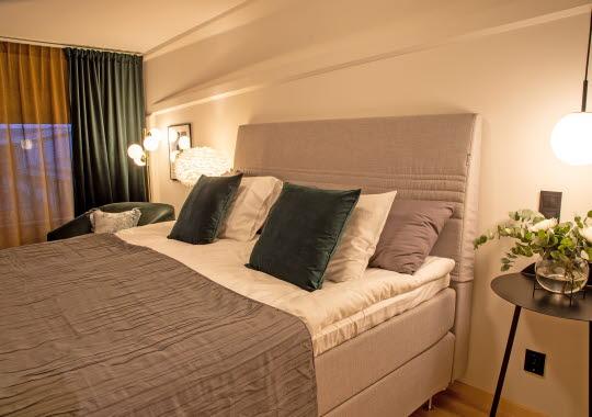 Säng med grå tyggavel, gröna gardiner och kuddar.