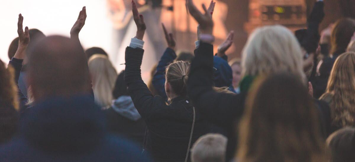 Publik framför en scen som applåderar med händerna i luften