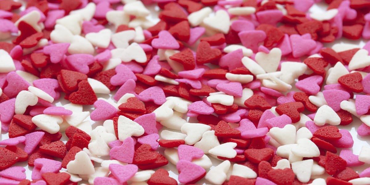 Massa små vita, rosa och röda hjärtan.