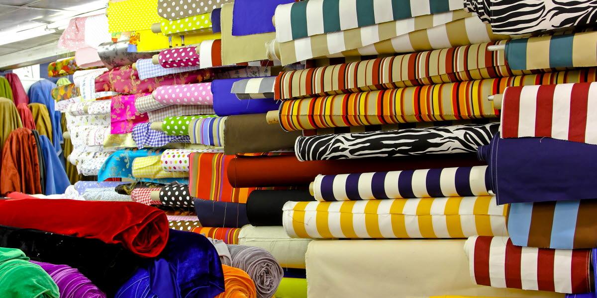 Vy över flera rullar med tyger i olika färger i en tygaffär.