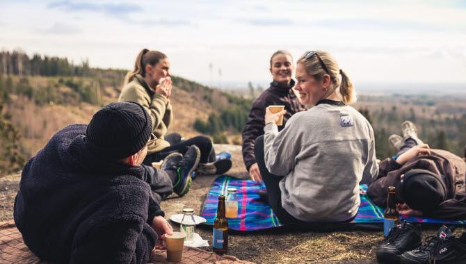 Personer som sitter och äter i naturen på en klippa.
