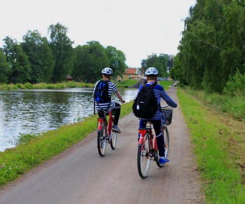 Två killar cyklar längs Göta kanal.