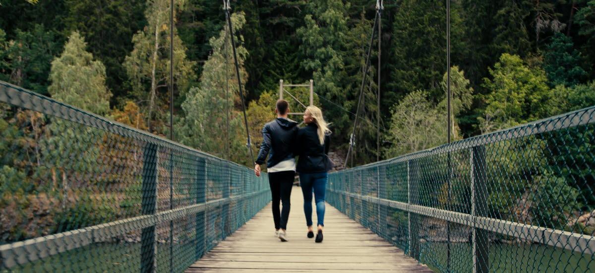 Ett par som går över en gångbro mot en skog