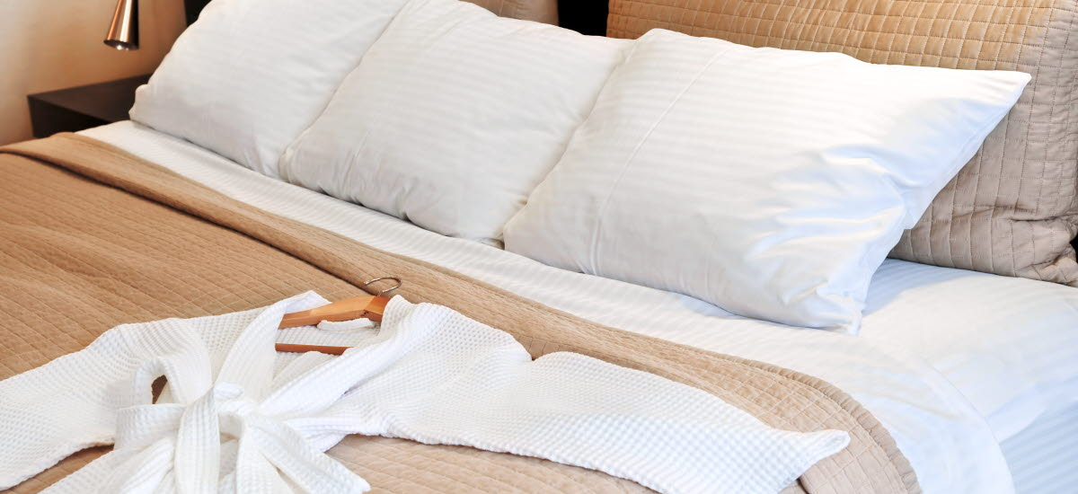 Hotellsäng som är bäddad med en vit morgonrock utlagd på sängen.