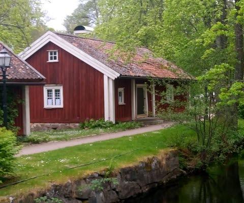 Röd liten trästuga med vita knutar i sommarskrud med ån Tidan framför på Turbinhusön i Tidaholm.