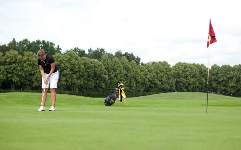 En kvinna står och ska putta på golfbanan vid Bjertorp i Vara.