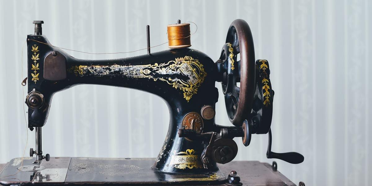 En antik symaskin i svart med färgade, målade mönster och en gulbrun trådrulle, är monterad på ett polerat, brunt träbord.