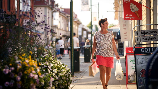 En kvinna som är nöjd med sin shopping en sommar i Lidköping.
