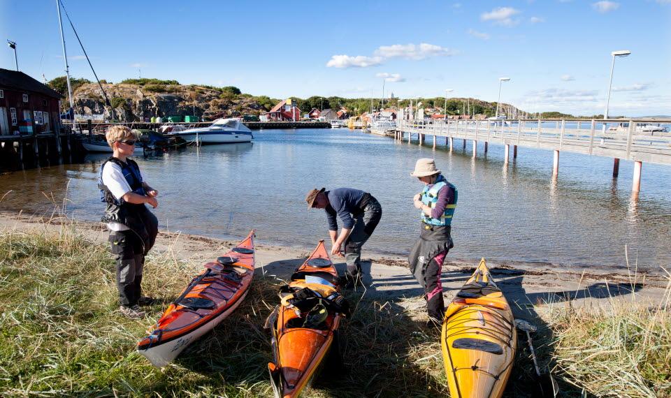 Tre färgglada kajaker ligger uppdragna på en liten strand vid Långegärde på Sydkoster. De som skall paddla förbereder sig för att ge sig ut på havet.