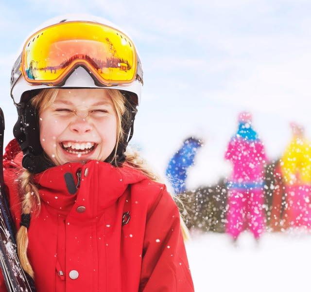 Flicka i röd jacka ler med hela ansiktet. Håller sina skidor i famnen.