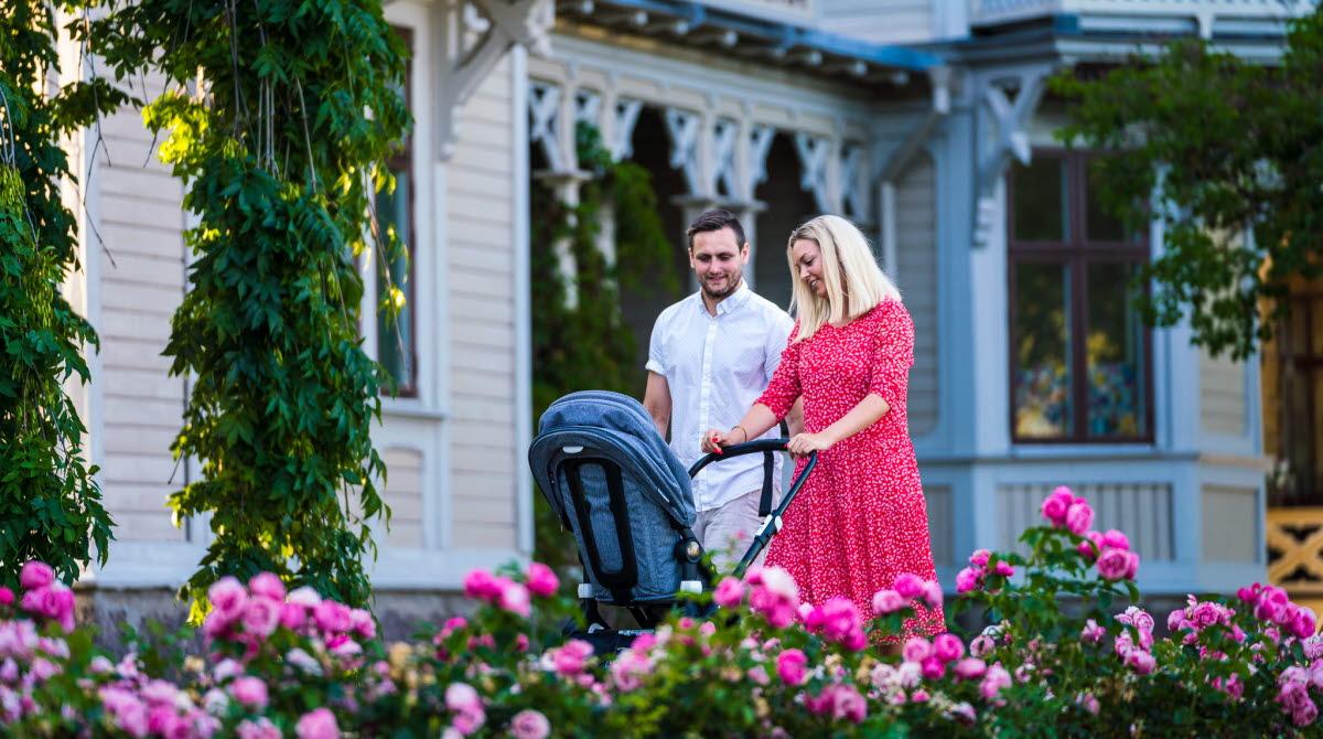 Par med barnvagn promenerar i Hjo Stadspark.