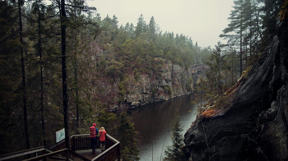 Två vandrare står på en plattform i trä och tittar ut över ett smalt sund med branta bergsväggar på sidorna