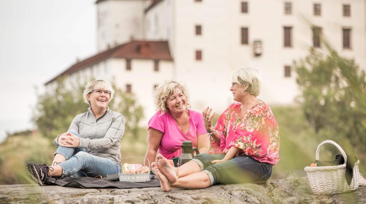 Några kvinnor som sitter framför Läckö Slott