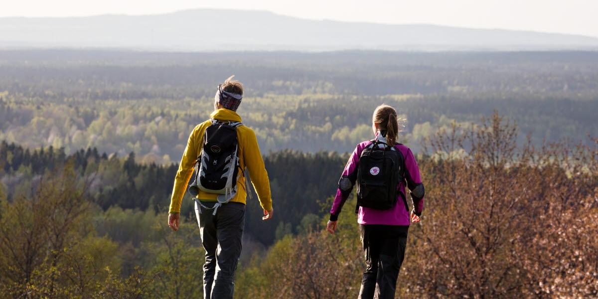 Två personer i färgglada kläder vandrar bort från kameran med en vindunderlig utsikt över Vallebygden.
