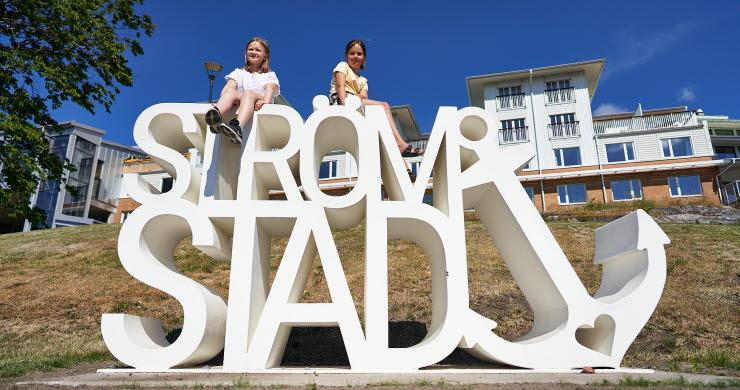Två tjejer sitter på Strömstad varumärke ute Laholmen