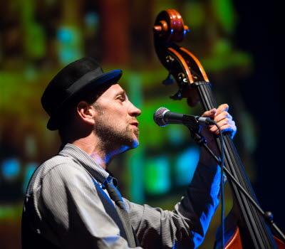 En man som spelar på basfiol och sjunger.