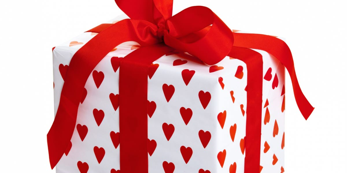 Ett paket med vitt papper med röda hjärtan och rött sidenband runt paketet med en rosett ovanpå.