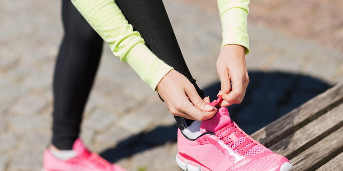 En person som knyter sina rosa träningsskor.