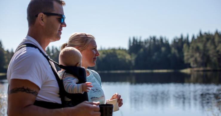 Par tittar ut över en sjö med kaffekoppar i handen på Hökensås utanför Tidaholm.
