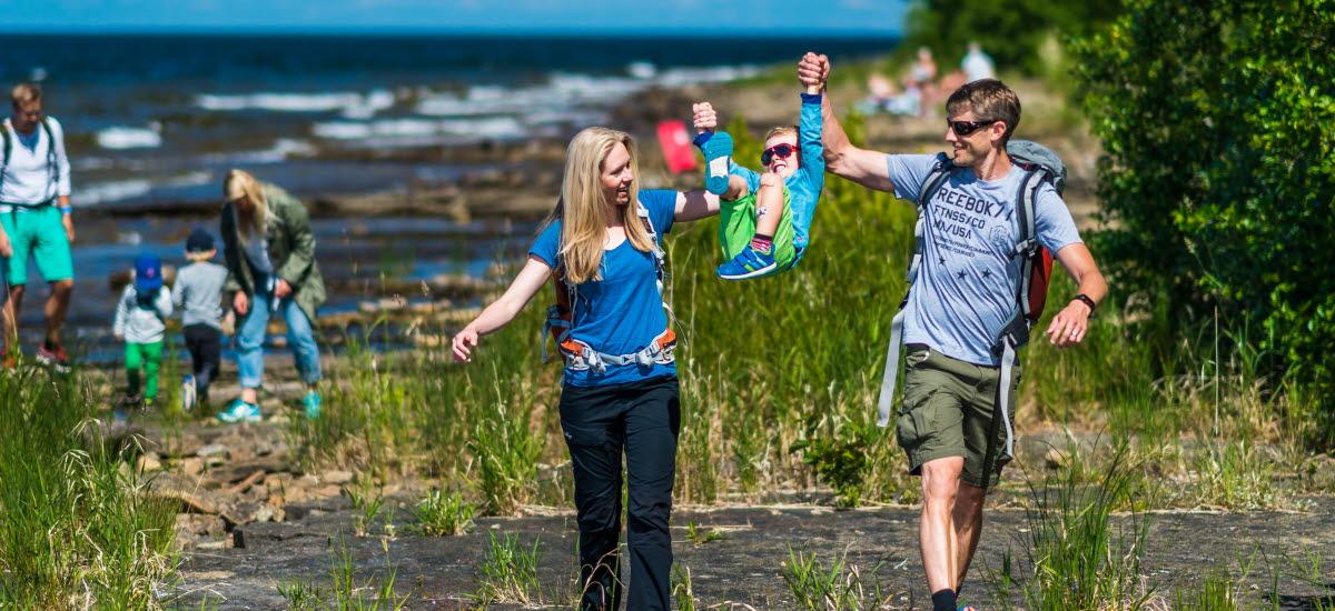 En mamma och en pappa lyfter upp sin son i händerna i framtraskande på klipporna längs med strandkanten.
