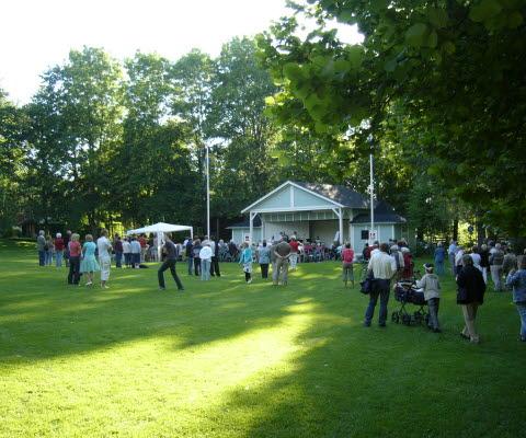 Personer som står och lyssnar och tittar framför en scen på Turbinhusön på evenemanget som heter Skoj på ön.