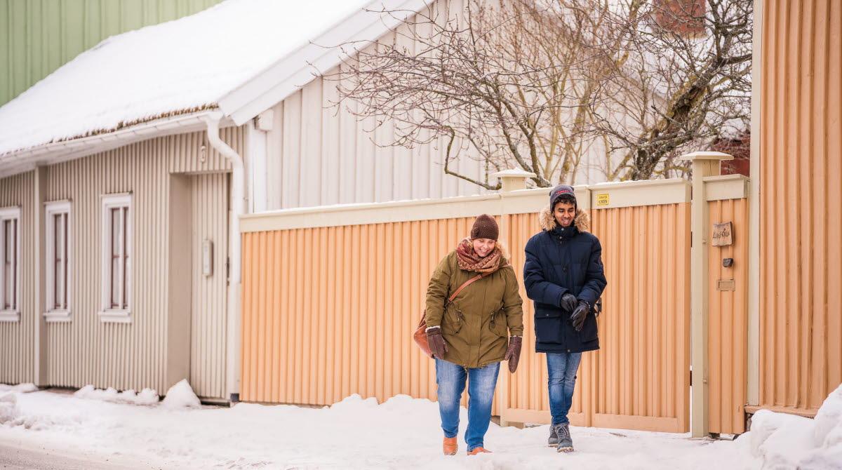 Två människor promenerar längs en gata i trästaden Hjo vintertid.
