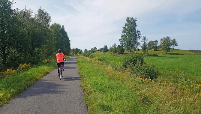 kvinna i organge tröja som cyklar på asfaltsbelagd cykelbana i gröna omgivningar.