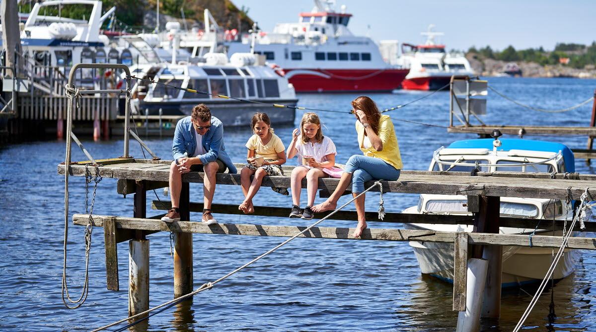 Familj sitter på brygga i centrala Strömstad